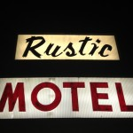 A welcoming view for weary travelers: The Rustic Motel sign lit up at night.